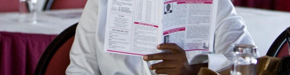 "A Rotarian reads the ""Muyenga Reporter,"" the newsletter of the Rotary Club of Muyenga, Uganda, before a club meeting."