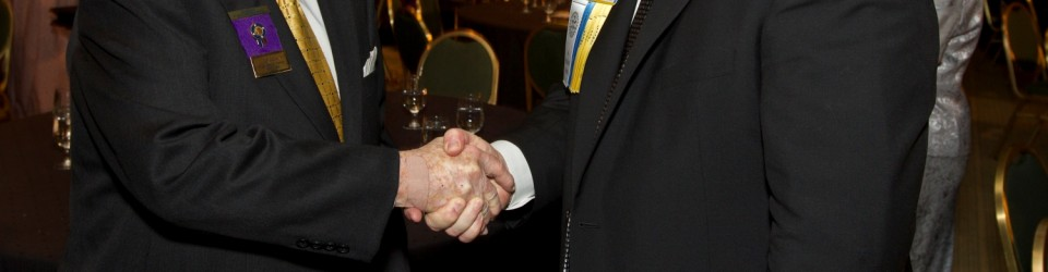 1987-88 RI President Charles Keller and 2012-13 RI President-elect Ron Burton shake hands at the  International Fellowship Dinner and Dance. International Assembly, 17 January 2012, San Diego, California.